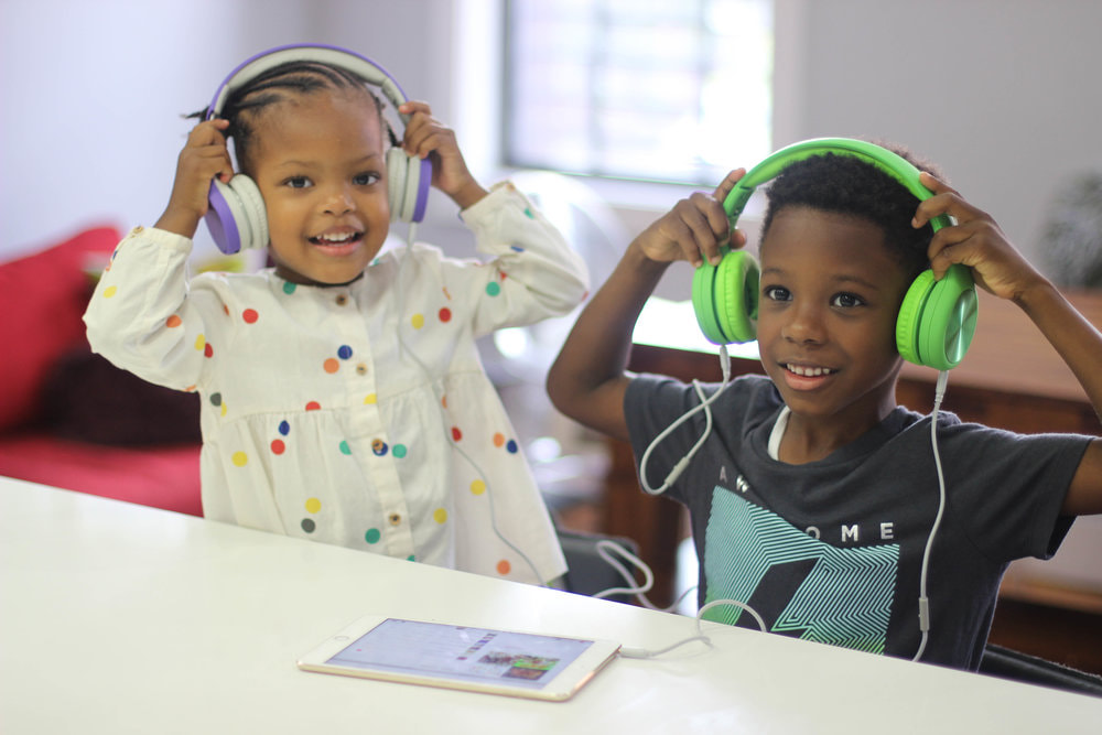 Two kids with headphones, smiling and looking at camera